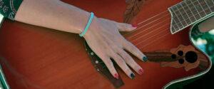 Mano sobre guitarra - Alyta actuando